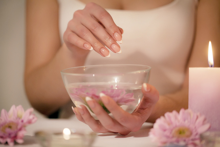 Closeup shot of a woman in a nail salon receiving a manicure by a beautician with cotton wool with acetone. Woman getting nail manicure. Beautician file nails to a customer