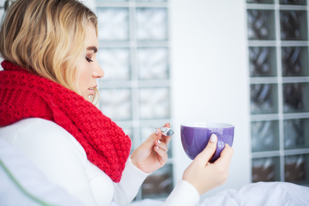 High temperature. Sick woman sitting under a blanket