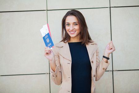 Vacation. Woman near airport holds air tickets and passport Stockfoto