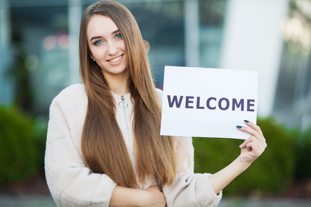 Women business with the poster with welcome message Foto de archivo