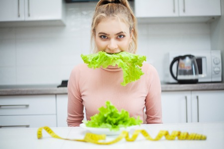 Green diet. Young beautiful woman eating healthy food - salad