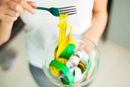 Diet and health concept. Woman hands holding bowl with measuring tape