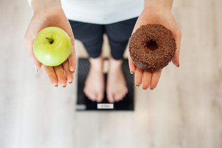 Diet. Woman Measuring Body Weight On Weighing Scale Holding Donut and apple. Sweets Are Unhealthy Junk Food. Dieting, Healthy Eating, Lifestyle. Weight Loss. Obesity. Top View Stock fotó