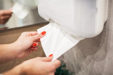 Distributore di asciugamani di carta. La mano della donna prende il tovagliolo di carta in bagno Archivio Fotografico