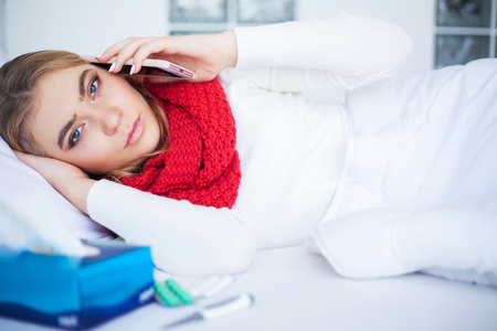 Woman with flu virus lying in bed, she is measuring her temperature with a thermometer Stock Photo