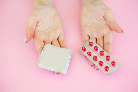 Pills or Condom. Antibiotics from venereal diseases. Concept of safe sex. Pills and condom lie on a pink Background. Imagens