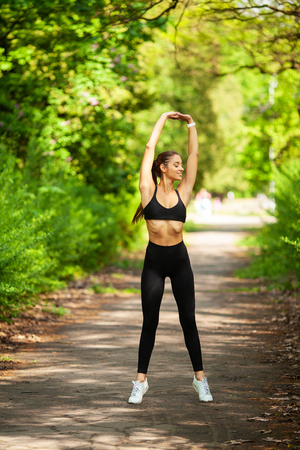Girl doing sport. Young Female Exercising in a Park