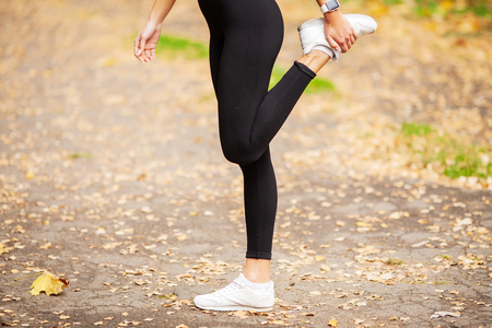 Fitness Girl. Young fitness woman runner stretching legs before run. 写真素材