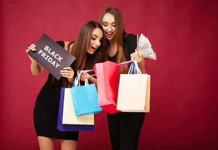 Shopping. Elegant brunette womans wears black dress holding shopping bags, black friday concept 写真素材