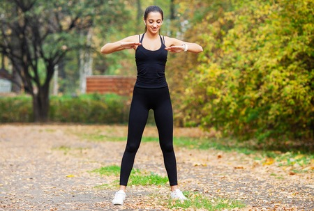 Fitness Girl. Young woman doing exercises in the park.