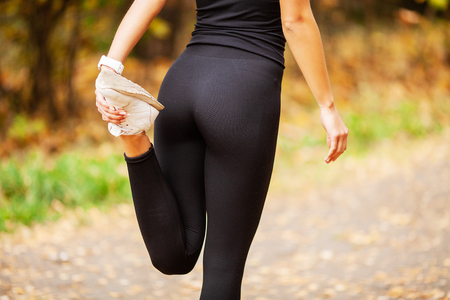 Fitness Girl. Young fitness woman runner stretching legs before run