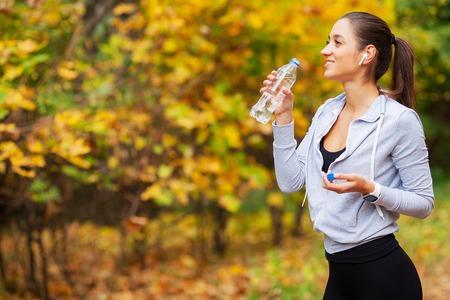 Fitness Girl. Young beautiful woman in sportswear drinking water in park 写真素材