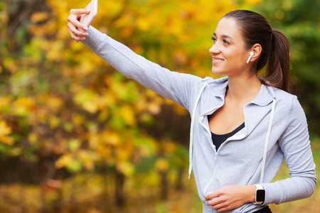 Fitness. Sport woman taking selfie photo on mobile phone in summer park 写真素材
