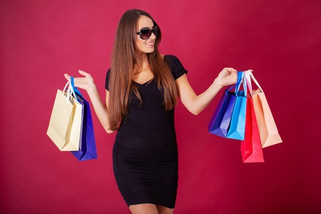 Shopping. Pretty young woman stylishly dressed in black with bags after shopping