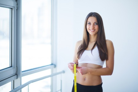Diet. Portrait of beautiful young woman measuring her figure size with tape measure