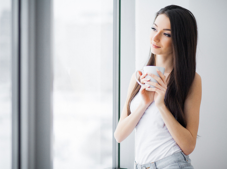 Happy morning. Portrait of beautiful young woman standing at window, drinking coffee and looking outside enjoys of rest 写真素材