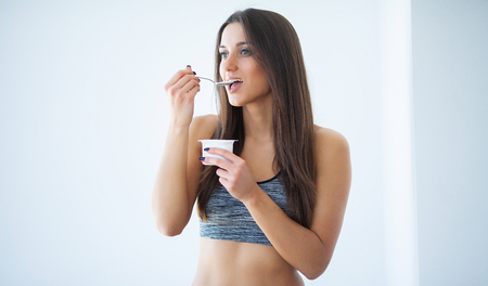Diet. Beautiful young woman eating yogurt in the kitchen at home 写真素材