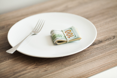 Money lying on the plate with fork. Dollars photo. Greedy corruption concept. Bribe idea.