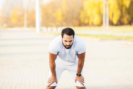 Aptitude. Homme de coureur épuisé se reposant sur le parc après l'entraînement
