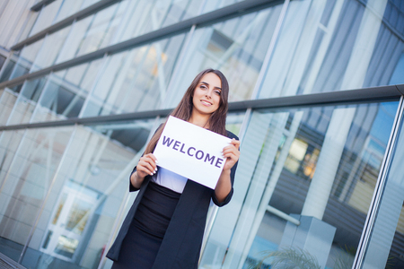 Travel. Women business with the poster with welcome message