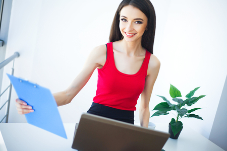 Office Business Woman Smiles and Holding Folder with Diagrams