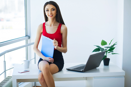 Office Business Woman Smiles and Holding Folder with Diagrams. W