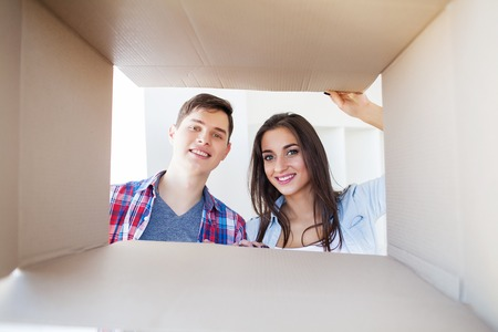 Young happy couple moving into their new home. They unpacking and cleaning new home Banco de Imagens - 122303662