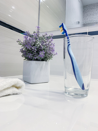 Clean toothbrush in a clear glass on bathroom countertop 版權商用圖片