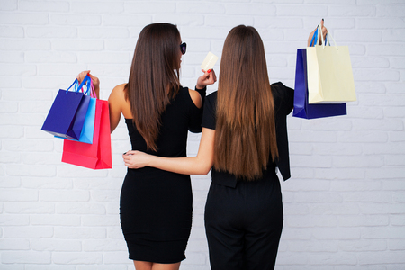 Shopping. Two women holding black bags on light background in black friday holiday Imagens