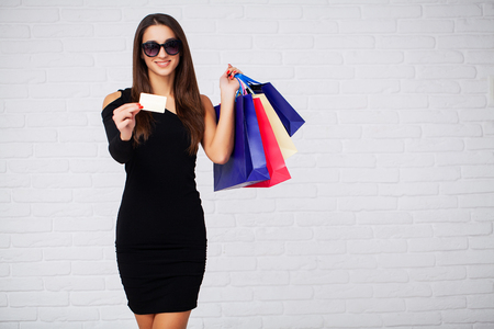 Shopping. Women holdingdiscount blanks on ligth background in black friday holiday