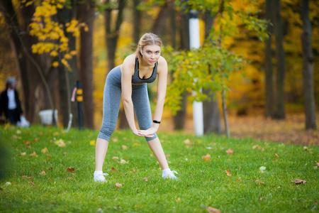 Geschiktheid. Vrouw doet stretching oefening op park