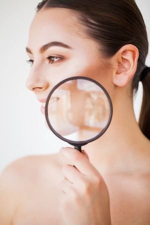 Woman Looking Through Magnifier And Smiling Close Up