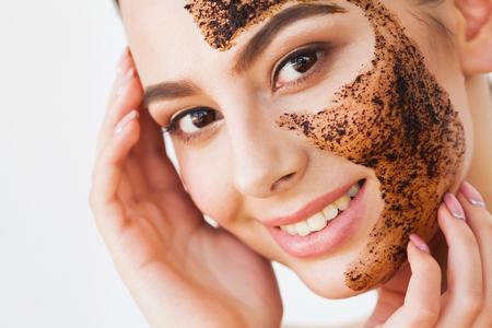 Exfoliante facial para la piel. Niña sonriente aplicando mascarilla de café exfoliante en la piel