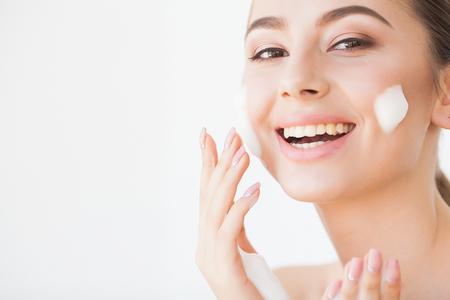 Schönheits-Gesichtspflege. Frau mit Creme auf der Gesichtshaut