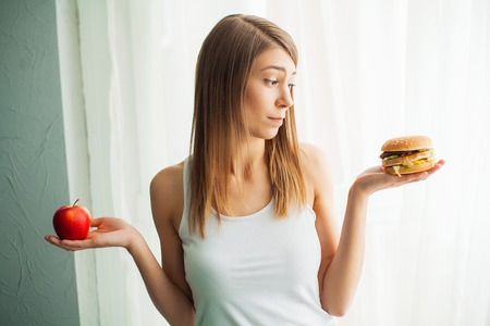 Dieting concept, beautiful young woman choosing between healthy food and junk food