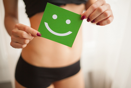 Women Health. Closeup Of Healthy Female With Beautiful Fit Slim Body In White Panties Holding White Card With Happy Smiley Face In Hands. Stomach Health And Good Digestion Concepts Stock Photo