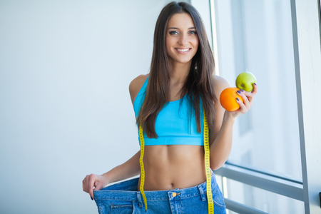 Diet. Woman shows her weight loss and wearing her old jeans Stock Photo