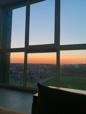 Panoramic windows overlooking beautiful golden sunset. View from home window