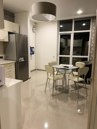 Modern light interior of kitchen with white furniture and dining table