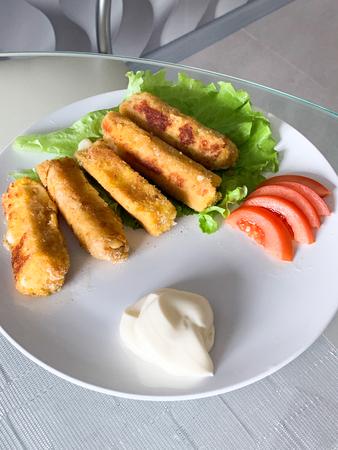 Fried mozzarella cheese sticks breaded on white plate