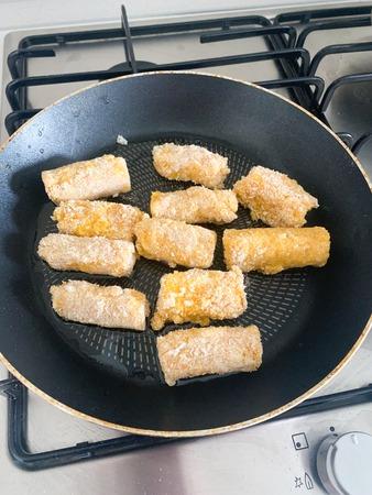 Fried mozzarella cheese sticks breaded on frying pan 写真素材