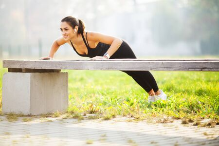 Healthy lifestyle. Sports woman doing exercises on bench and listening to music in the urban environment