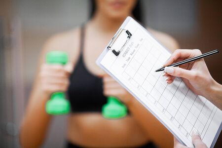 Fitness plan. Sports trainer amounts to workout plan close-up 写真素材