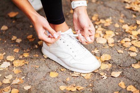 Fitness. Woman Runner Tightening Shoe Lace. Runner Woman Feet Running On Road Closeup On Shoe