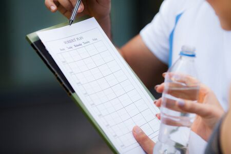 Fitness plan. Sports trainer amounts to workout plan close-up Stock Photo