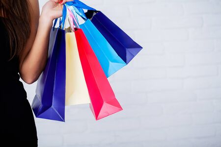Shopping. Closeup of woman holding color paper shopping bag on white wall background 写真素材 - 124619145