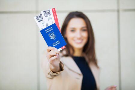 Podróż. Kobieta trzymająca dwa bilety lotnicze w paszporcie za granicą w pobliżu lotniska