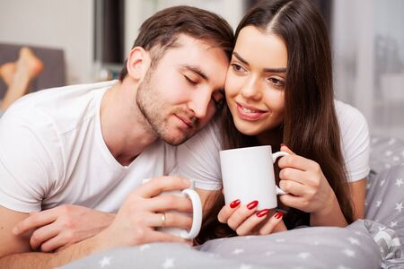 Happy couple having fun in bed. Intimate sensual young couple in bedroom enjoying each other