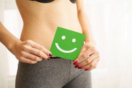 Frauengesundheit. Nahaufnahme der gesunden Frau mit dem schönen schlanken Körper des Sitzes im schwarzen Schlüpfer, der grüne Karte mit glücklichem Smiley-Gesicht in den Händen hält. Magengesundheit und gute Verdauungskonzepte. Hohe Auflösung