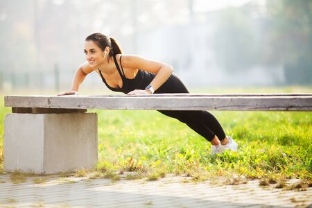 Healthy lifestyle. Sports woman doing exercises on bench and listening to music in the urban environment Stock Photo